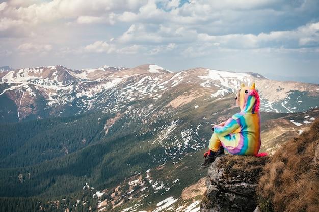 Путешественник в костюме единорога высоко в горах
