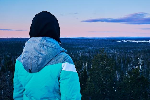 Путешественница, глядя с горы на холодный утренний зимний лесной пейзаж