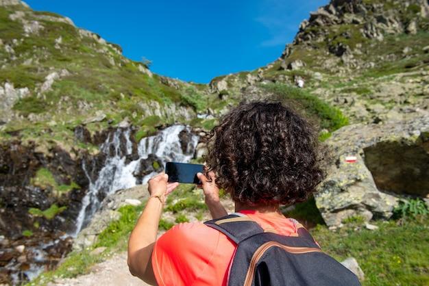 野生の水しぶきの滝の近くの女性ハイカー