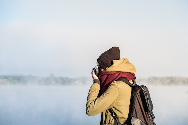 Путешественник женского пола фотографируя красивые пейзажи природы покрытые туманом. женщина использует старинную пленочную камеру, стоя в великолепном природном парке на рассвете