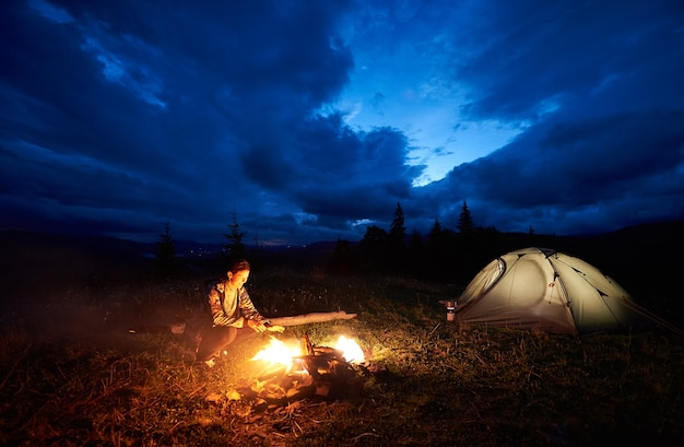 Female hiker resting at night camping