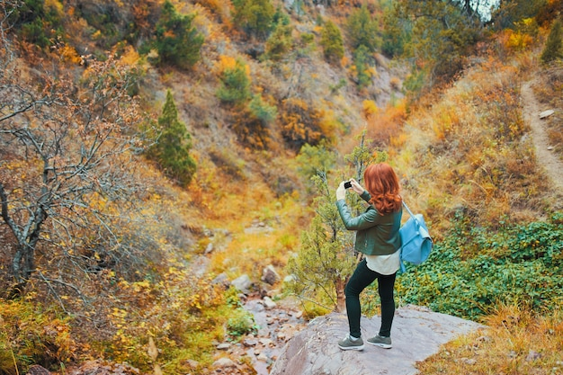 Female hiker taking selfie in mountains forest. woman tourist with a backpack admires the mountain rock.