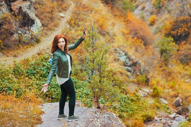 Female hiker taking selfie in mountains forest.