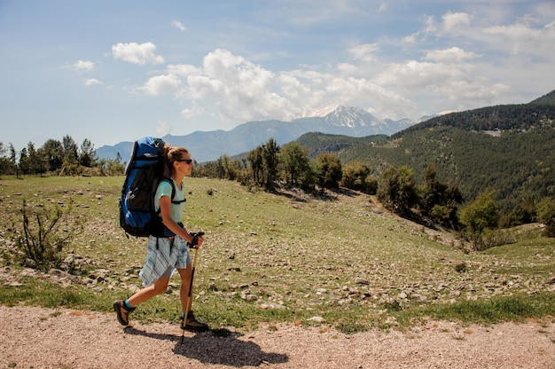 Female hiker travelling up the road in hills