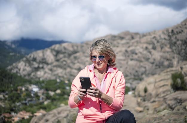그녀의 전화를 사용 하 고 아름 다운 경치의 사진을 찍는 여성 등산객