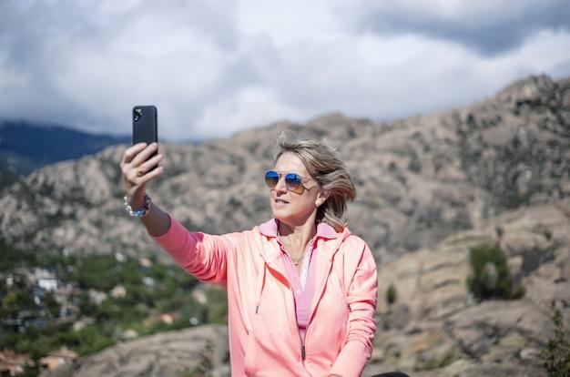 Escursionista femminile che usa il suo telefono e scatta foto della bellissima vista