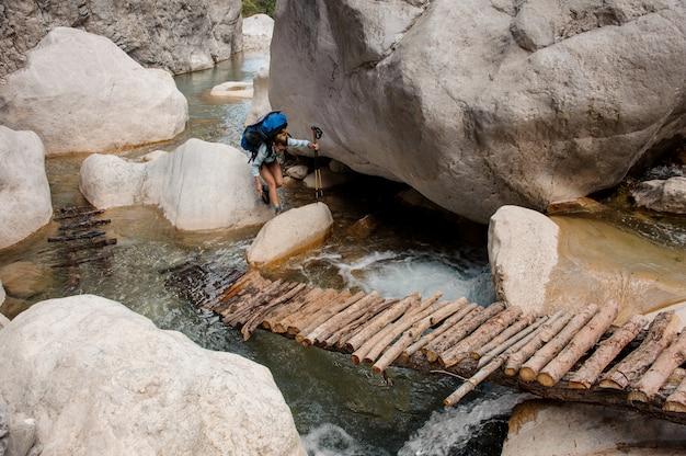 Female hiker wades through river between cliffs