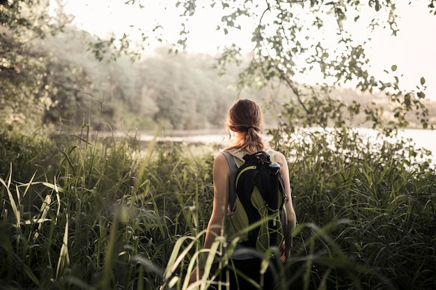 Female hiker walking in the green grass near the lake