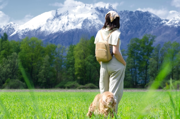 犬と一緒に緑の野原を歩き、雪をかぶった山々を見ている女性ハイカー