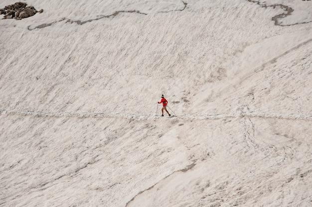 山の杖でさまよう女性ハイカー