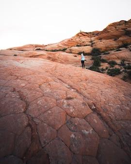 岩が多い砂漠の丘の上のバックパックを持つ女性ハイカー
