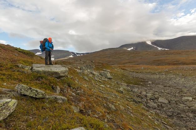 Female hiker with backpack at kungsleden trail admiring nature of sarek