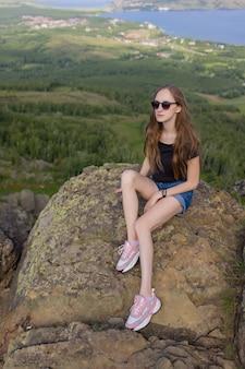 日中の景色を楽しんで山の頂上に座っているバックパックを持つ女性のハイカー。 Premium写真