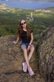 日中の景色を楽しんで山の頂上に座っているバックパックを持つ女性のハイカー。