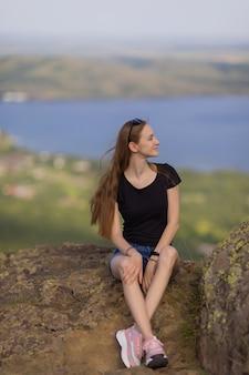 배낭을 메고 산 꼭대기에 앉아 낮 동안 전망을 즐기는 여성 등산객.