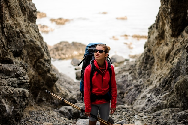 Female hiker with backpack stands between cliffs