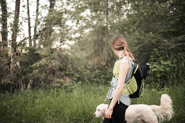 森林を歩いている彼女の犬との女性の登山人