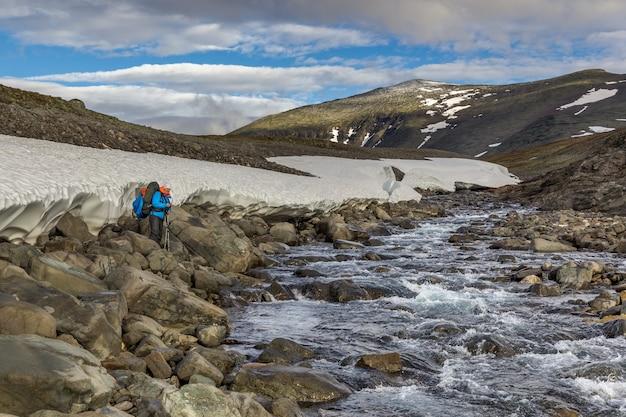 산 강을 건너는 여성 등산객 위트 배낭