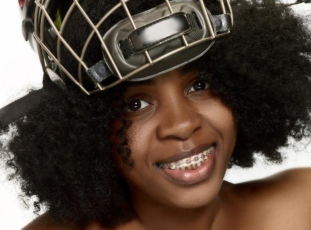 여성 하키 선수는 흰색 스튜디오 벽에 헬멧과 마스크를 닫습니다