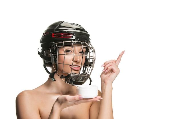 Giocatore di hockey femminile in casco e maschera sopra la parete bianca dello studio