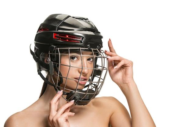 헬멧에 흰색 스튜디오 배경 위에 마스크 여성 하키 선수. 크림을 가진 젊은 여자. 미용, 피부 및 얼굴 보호 개념