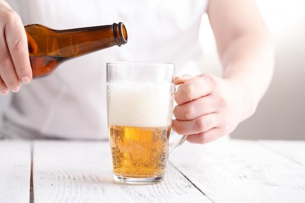 女性は白いテーブルの上のガラスのマグカップでビールを保持します。