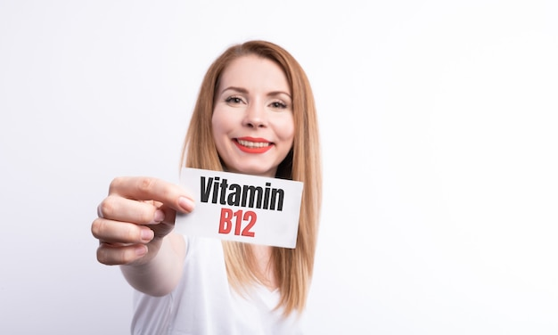 Female hold a card with word vitamin b12 on white.