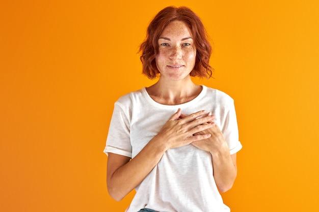 Женщина держится за руки на груди и смотрит в камеру, рыжая веснушчатая женщина в повседневной одежде изолирована