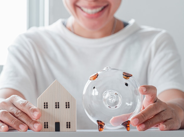 Female hold home model and piggy bank on the white table and smile face of woman background