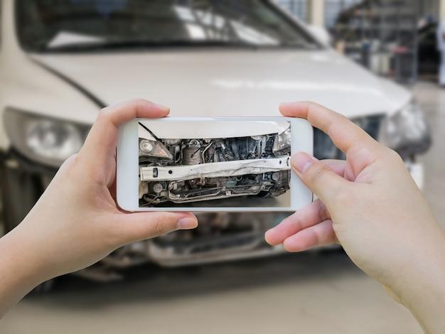 女性は保険のために自動車事故を撮影するモバイルスマートフォンを保持します