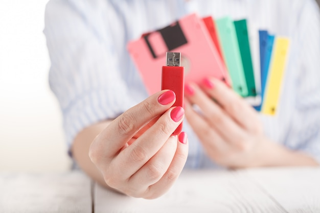 Female hold old floppy disk and modern flash drive