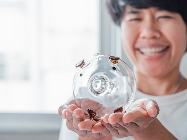 Female hold a piggy bank and smile face of woman background