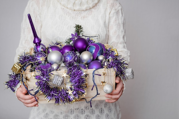 紫色のクリスマスの飾りでいっぱいの箱を持っている女性