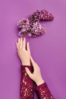 咲くライラックの枝を保持している女性