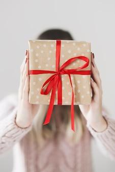 赤いリボンと水玉のクラフト紙で包まれたクリスマスギフトボックスを保持している女性
