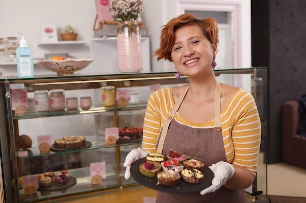 Женщина держит тарелку с вкусными сырыми десертами