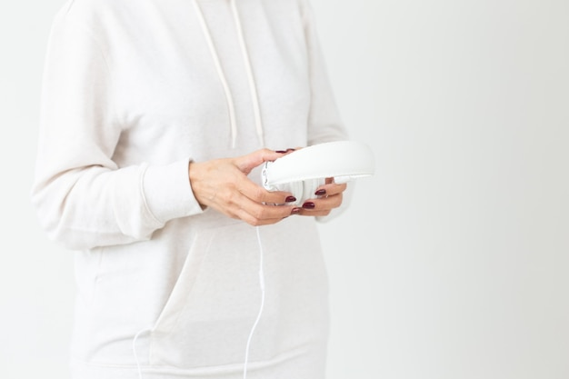 白い壁に大きなヘッドフォンを保持している女性