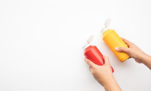 白い背景の上のボトルソースを保持している女性