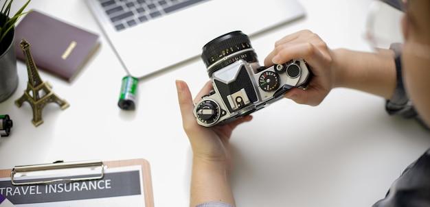 Женщина держит камеру при подготовке пунктов путешествия на белом столе с ноутбуком и формы страхования путешествий