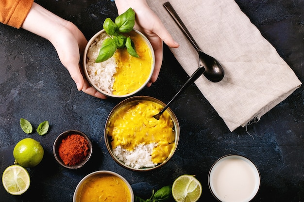 Female holding ceramic bowl of yellow curry served with basil and limes
