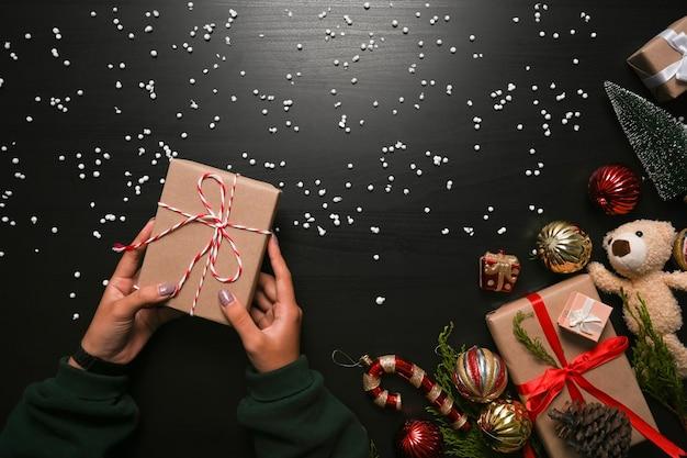 Female holding christmas gift box on dark background.