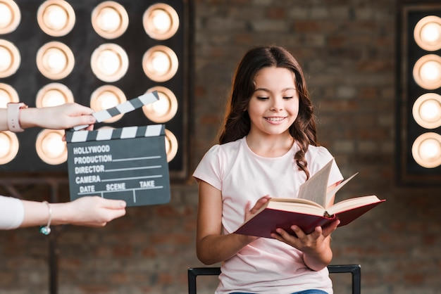 Female holding clapper board in front of girl reading book