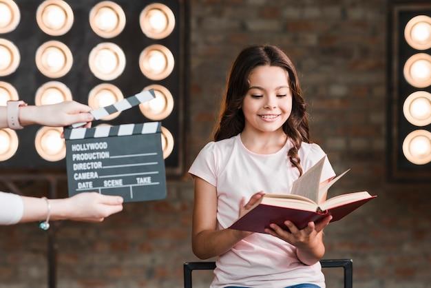 Женщины, держащая колотушку перед книгой чтения девочки
