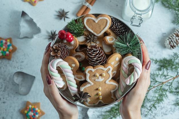 手に食器を持っている女性。クリスマスのクッキーと装飾でいっぱいの食器。