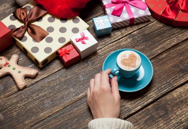 Женщина держит чашку кофе на деревянном столе возле рождественских подарков