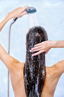 Female holding douche and washing hair