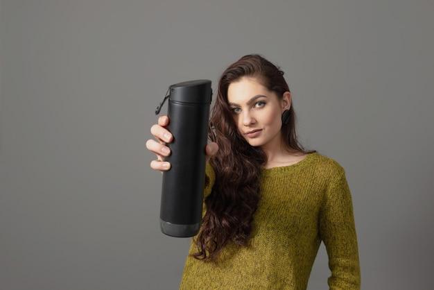 飲み物のリマインダー、健康的なライフスタイルの概念とエコ再利用可能なスマートサーモウォーターボトルを保持している女性