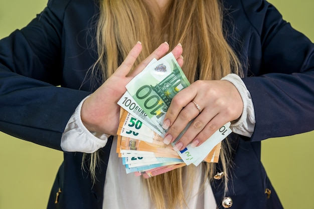 Female holding euro in her hands isolated on green wall