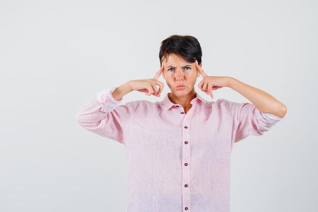 Femmina che tiene le dita sulle tempie in camicia rosa e sembra intelligente. vista frontale.
