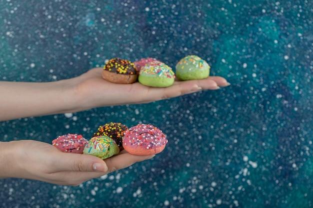 青いテーブルに手で新鮮なクッキーを保持している女性。